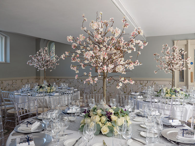 Blossom tree table centres in dining area of Ellenborough Park hotel for a wedding feast