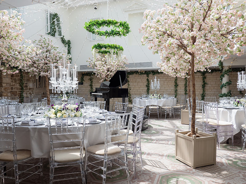 Blossom trees inside dining room at a wedding reception at Ellenborough Park, Cheltenham