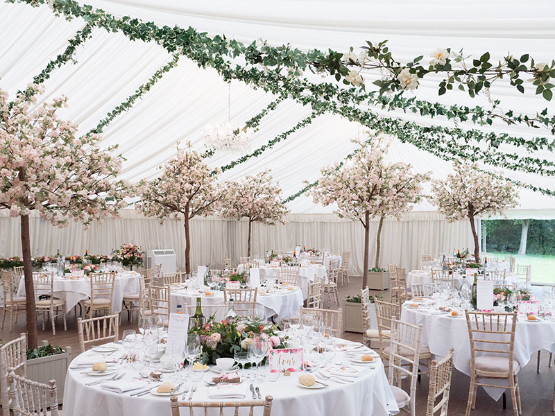 Blossom trees indoors at a marquee wedding party at Stanbrook Abbey