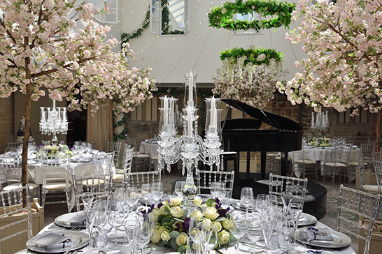 Ellenborough Park wedding, inside the main dining room, crystal candelabra, piano and blossom trees