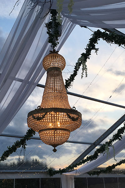 Stunning close-up photo of a 2 meter Empire Chandelier in an outdoor wedding installation at sunset