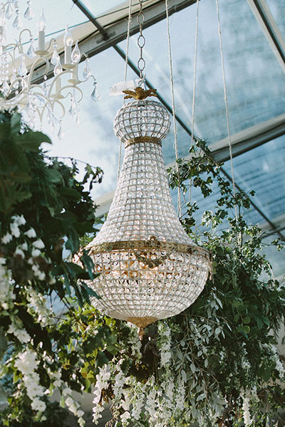 Stunning 90cm Empire chandelier in an outdoor clear marquee surrounded by greenery