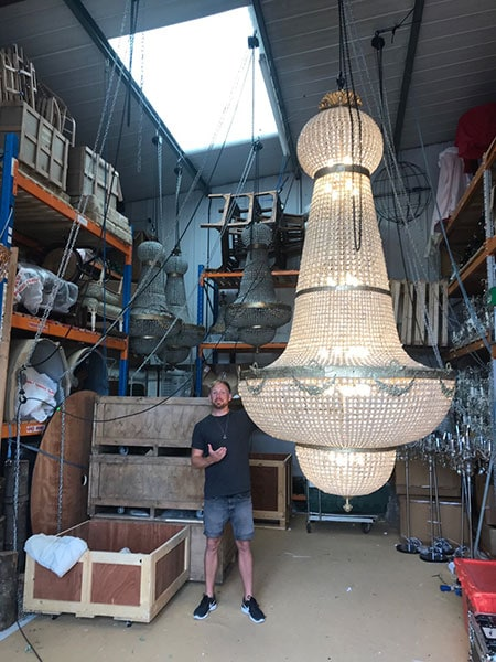Laurie standing next to 3.5m Empire Chandelier in wareghouse to show scale